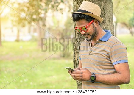 Happy indian guy looking his mobile phone and smiling - Young asian man texting online in park outdoor - New technology trends addiction concept - Warm filter with focus on face
