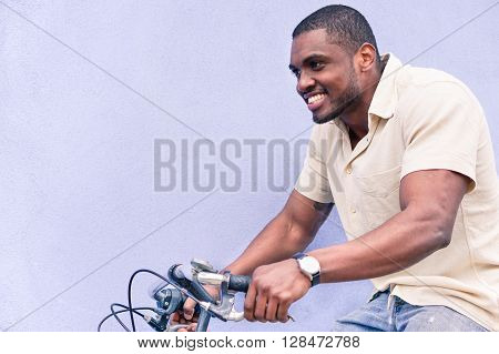 A happy African American man riding old style bicycle outdoor - Hipster black guy having fun - Healthy lifestyle and happiness concept - Warm vintage filtered look - Focus on face