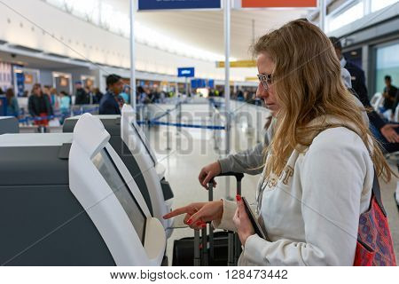 NEW YORK - MARCH 22, 2016: woman use check-in kiosk in JFK airport. John F. Kennedy International Airport is a major international airport located in Queens, New York City, United States.