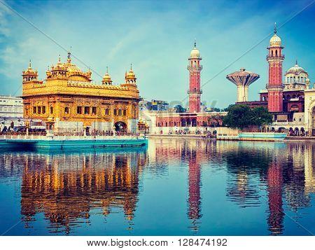 Vintage retro effect filtered hipster style image of famous indian toursit landmark and sacred pilgrimage site - Sikh gurdwara Golden Temple (Harmandir Sahib). Amritsar, Punjab, India