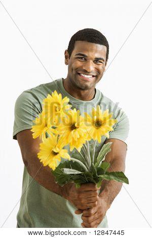 Sorrindo americano Africano macho segurando buquê de flores amarelas a pessoa invisível.