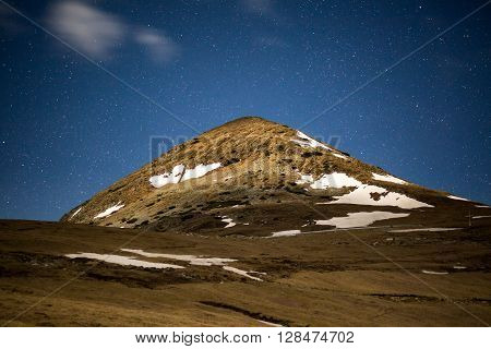 Landscape with a mountain peak and stars at midnight