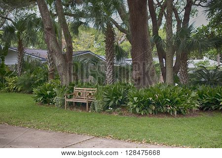 Scenic view of landscaped garden with wooden chair in foreground