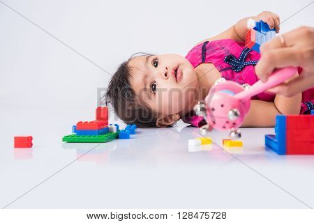 indian baby playing with toys or blocks, asian infant playing with toys on white background, indian baby girl playing with toys, indian toddler playing with toys, indian baby girl lying on white floor