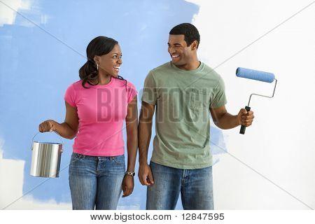 Fuentes de la afroamericana pareja sonriente al lado de la pared mitad pintado con pintura.