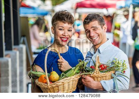 Smiling couple with baskets of produce at farmers market