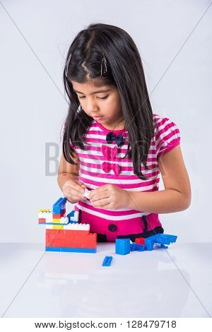 indian small girl or asian girl child playing with colorful blocks over white background, cute little indian girl constructing house with blocks, cute indian girl playing with toys