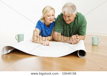 Middle-aged couple lying on floor looking at and discussing architectural blueprints together.