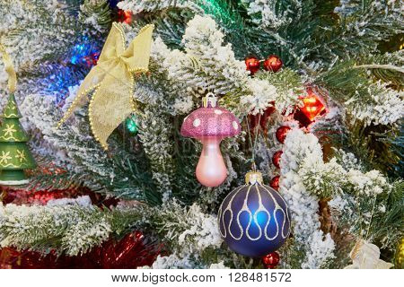 Decorative toys on branches of artificial christmas tree.