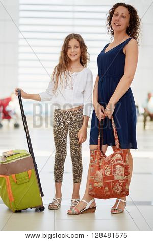 Mother and daughter stand in waiting hall at airport.