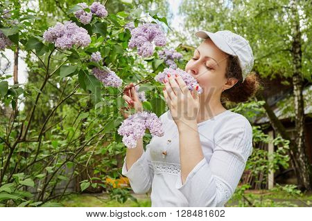 Young woman inhales the fragrance of lilacs.