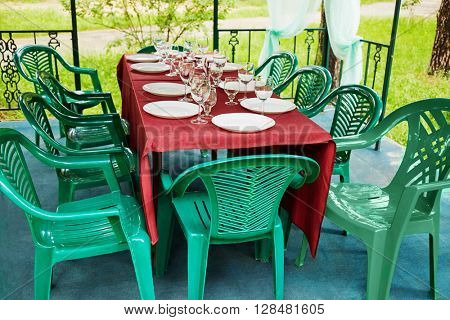 Decorated table, plastic furniture in pavilion of outdoor cafe.