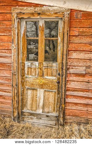 Door in need of painting on a weathered building in a ghost town