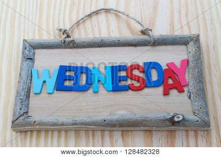 Wednesday word with colorful letter on Wood Background