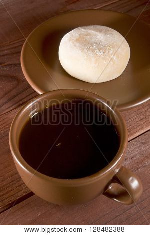 Traditional Japanese mochi on a brown saucer and cup with coffee