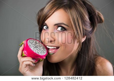 Headshot brunette, dark mystique look and green lipstick, holding open pink pitaya fruit next to mouth while sticking out tongue.