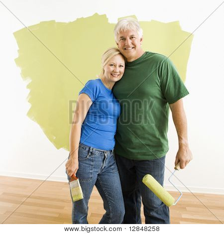 Middle-aged couple in front of wall they are painting green.