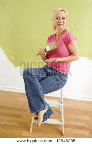 Portrait of smiling adult woman sitting in front of half-painted wall with paintbrush.