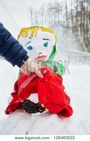 Male hand holds dress hem of burning stuffed Maslenitsa in winter park.