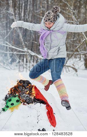 Woman jumps over burning stuffed Maslenitsa in winter park.