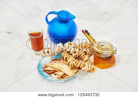 Blue jug and glass cup with beverage, bundles of cracknels, jar of honey, plate with pancakes on snow.
