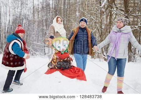 Family of four dance in a circle around burning stuffed Maslenitsa in winter park.