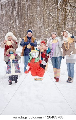 Six smiling people adults and children stand around stuffed Maslenitsa holding pancakes in hands at winter park.