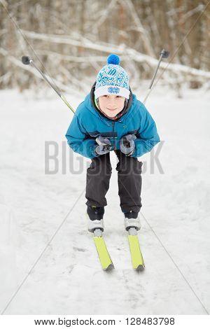 Teenage boy skis at snowy lawn in winter park.