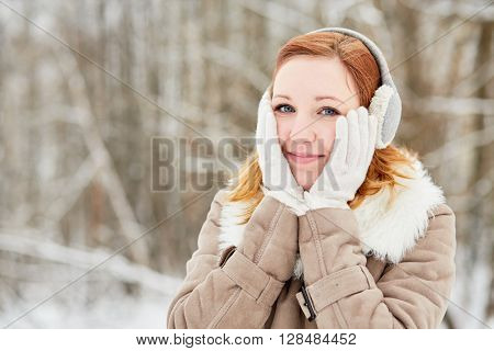 Humeral portrait of red-haired girl in earmuffs, clasping face with her hands in white knitted gloves.