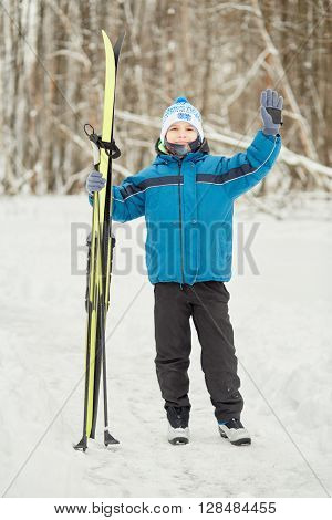 Teenage boy stands at snowy lawn in park holding skis and waving hand.