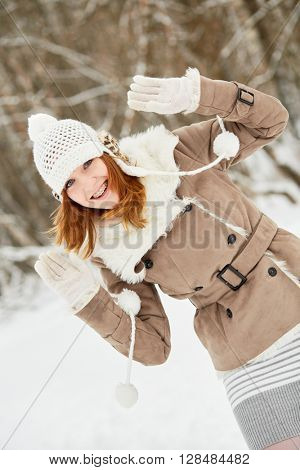 Red-haired smiling teenage girl with braces on teeth peeks out from side in winter park.