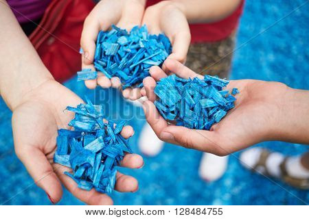 Woman and children hands holding wooden chips painted in blue for imitating water.
