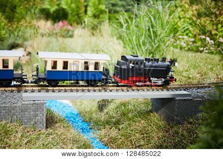 Toy train crosses bridge over artificial river in park.