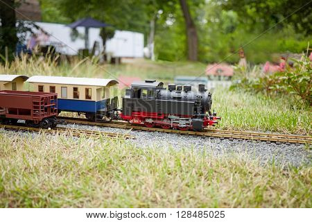 Layout of railway with locomotive and carriages in park.