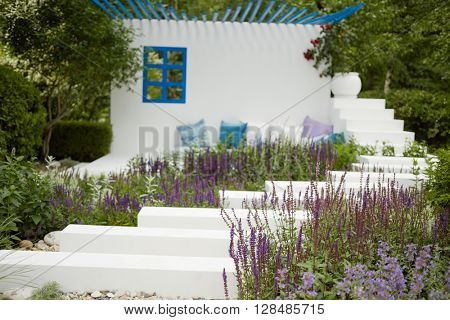 Steps with flowers at sides leading to wall with window, pillows and big flowerpot at summer park.