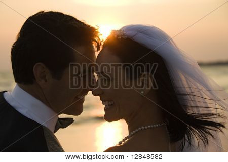 Newlyweds with their heads together in front of a setting sun on the beach. Horizontal shot.