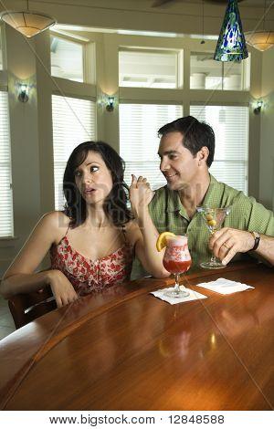 Woman dismisses an interested man at a bar.  Vertical shot.