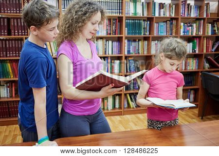 Mother and two children stand at table reading books in library.