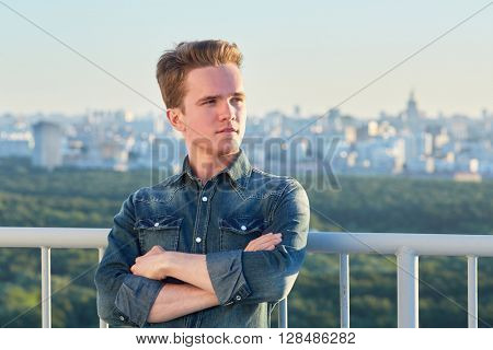 Portrait of young man in denim clothes stands crossing arms on chest on the roof leaning his back to the railing.