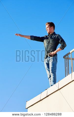 Young man in denim wear stands on the edge of the building roof outstretching one arm in front of him.