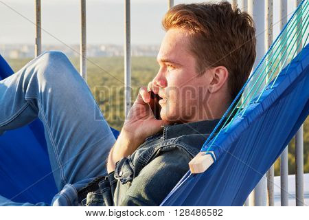 Closeup young man in denim clothes talks phone lying in hammock on building roof.