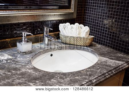 Wash bowl, mixing taps and basket with fresh towels in bathroom.