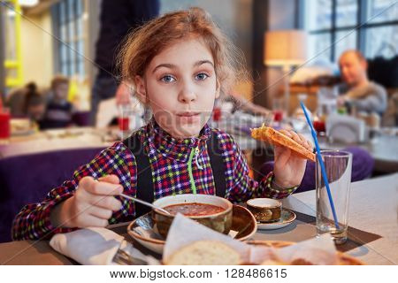 Girl eats first course sitting at table in cafe.