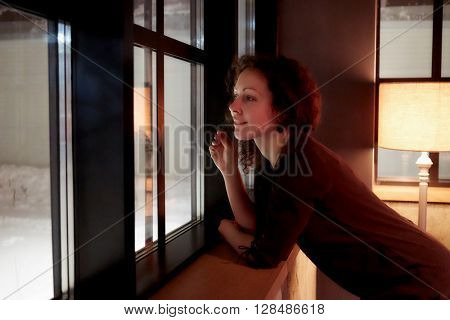 Young curly woman looks in window leaning her elbows on windowsill in room with torchiere.