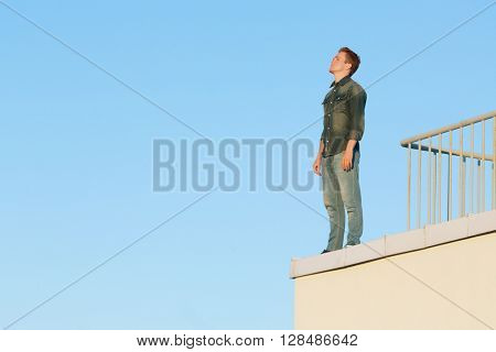 Young man in denim clothes stands on the edge of the building roof against blue sky.