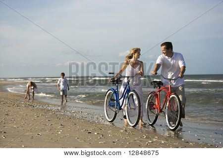 Husband and wife walk their bikes down the beach with children in the background. Horizontal shot.