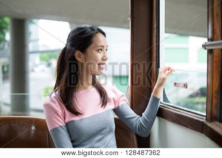 Lady riding on a tram and looking out the window