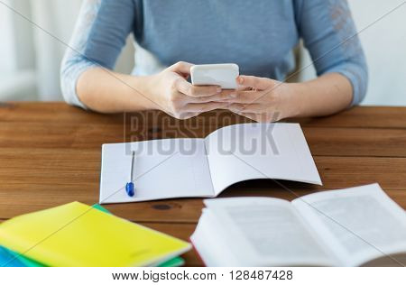 high school, education, people and learning concept - close up of young student or woman with smartphone, book and notebook at home