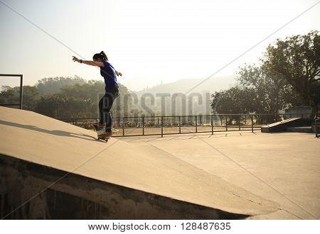 skateboarding woman riding skateboard at skatepark ramp