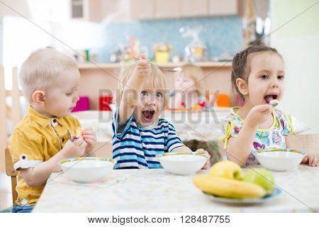 Funny little kid playing and eating in kindergarten